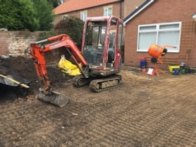 Digger excavating old driveway surface
