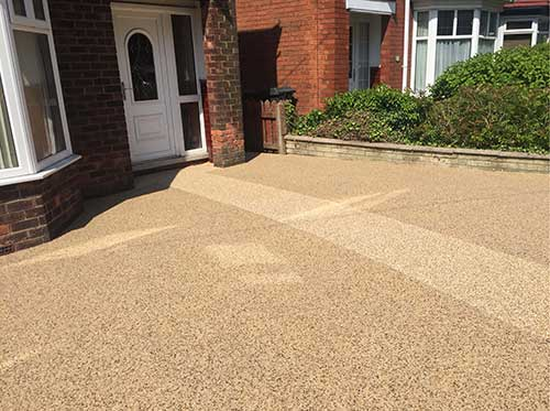 Light coloured resin driveway with contrasting path